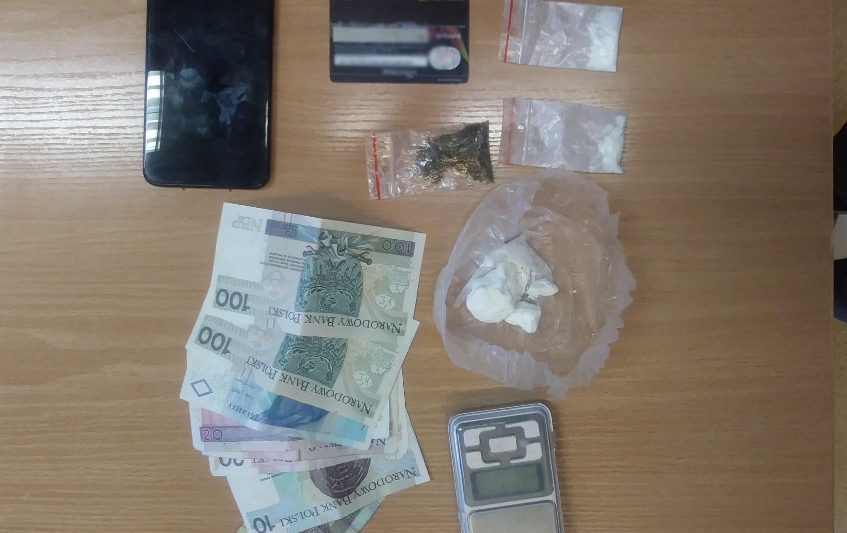 Zabezpieczone przedmioty Leżące na stole zabezpieczone przez policjantów narkotyki w woreczku, pieniądze, waga, telefon, karta płatnicza
