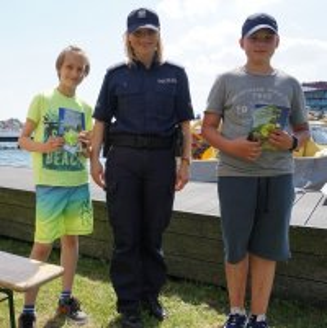 Policjantka z dwoma uczniami, którzy prawidłowo odpowiedzieli na pytania konkursowe