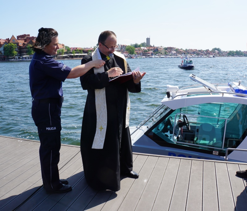 Ksiądz odmawia modlitwę tuż przed poświęceniem policyjnej łodzi