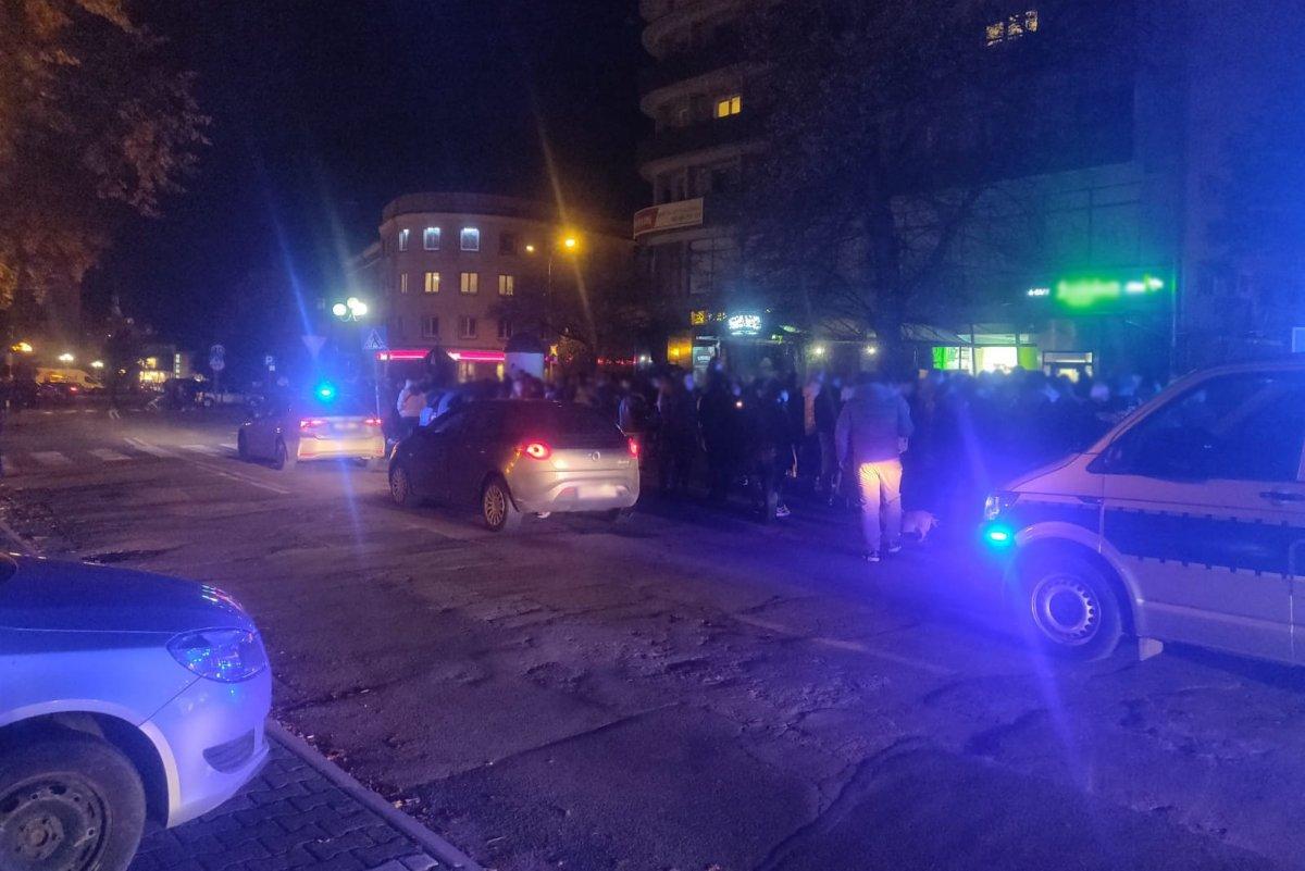 Policyjne radiowozy na miejscu nielegalnego zgromadzenia wieczorem na ulicy w Olsztynie, a za nimi uczestnicy zgromadzenia. Włączone sygnały świetlne radiowozów.